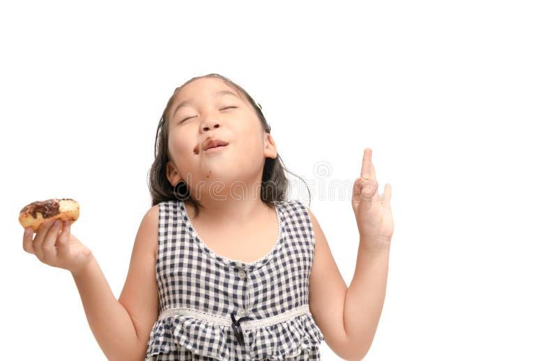 Маленькая счастливая милая девушка ест изолированный донут стоковое фото