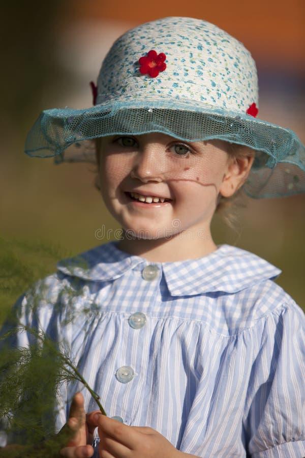 Маленькая усмехаясь девушка в голубой шляпе и платье страны стоковые изображения