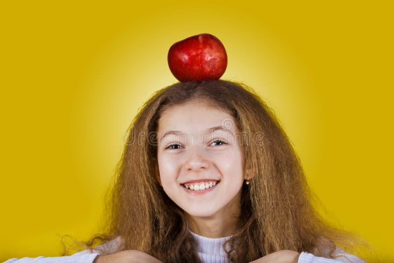 Маленькая школьница держа красное яблоко на ее голове над желтым ба стоковая фотография rf