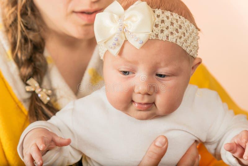 Маленькая newborn девушка со смычком на ее голове сидит ее матерью в ее оружиях стоковая фотография rf