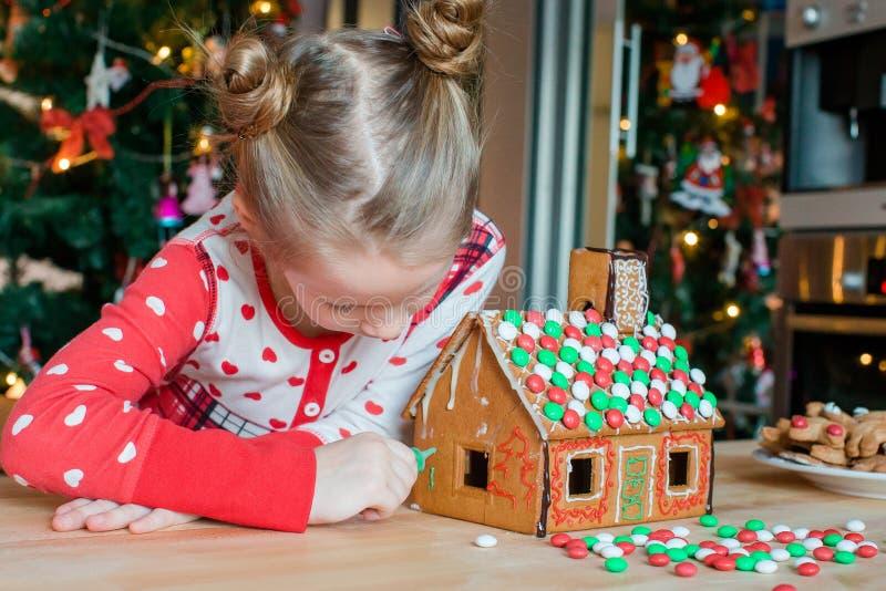 Маленькие девочки делая дом пряника рождества на камине в украшенной живущей комнате стоковая фотография