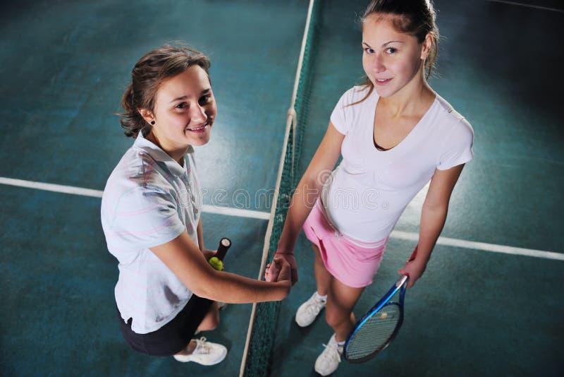 Маленькие девочки играя игру тенниса крытую стоковые фото