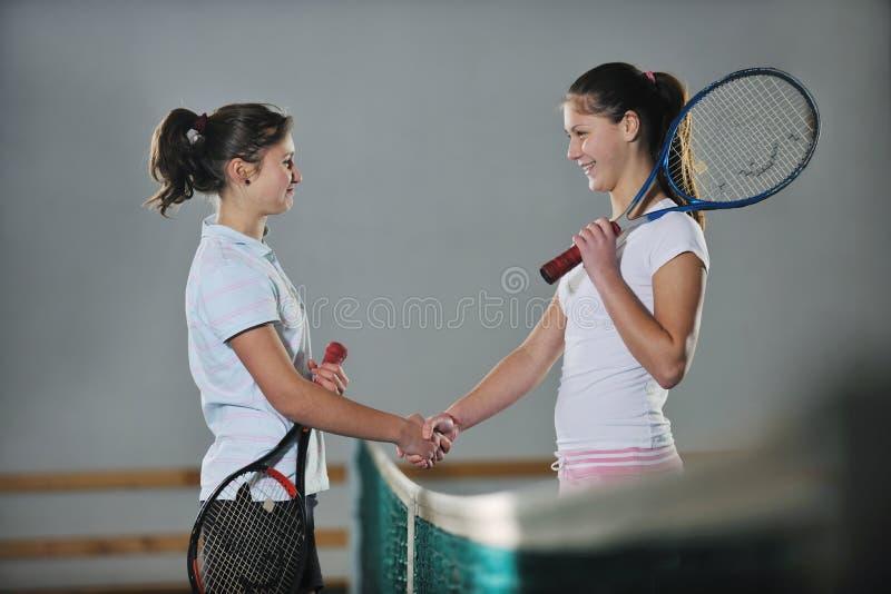 Маленькие девочки играя игру тенниса крытую стоковое фото