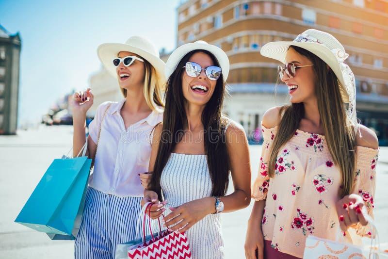 Маленькие девочки идя улица с хозяйственными сумками Счастливые покупки с улыбками стоковые изображения rf
