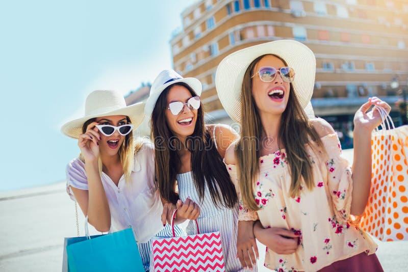 Маленькие девочки идя улица с хозяйственными сумками Счастливые покупки с улыбками стоковые фото