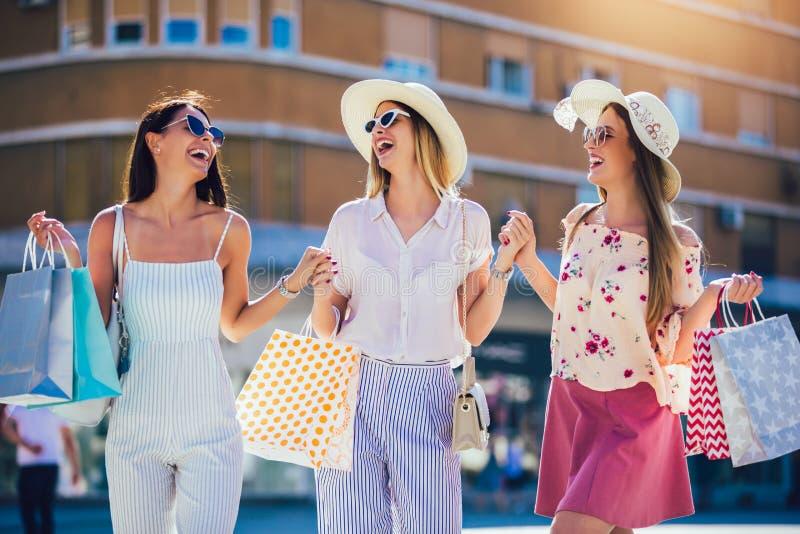 Маленькие девочки идя улица с хозяйственными сумками Счастливые покупки с улыбками стоковое фото rf