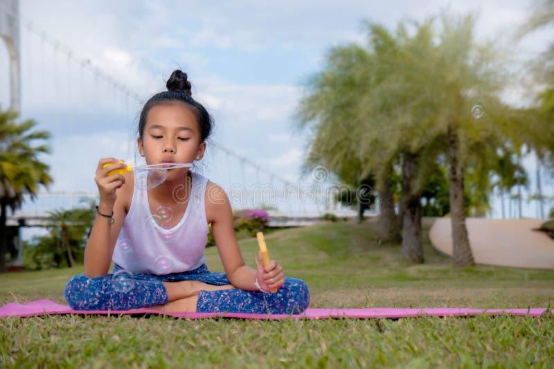 Маленькие девочки наслаждаются дунуть пузыри мыла в парке стоковые фотографии rf