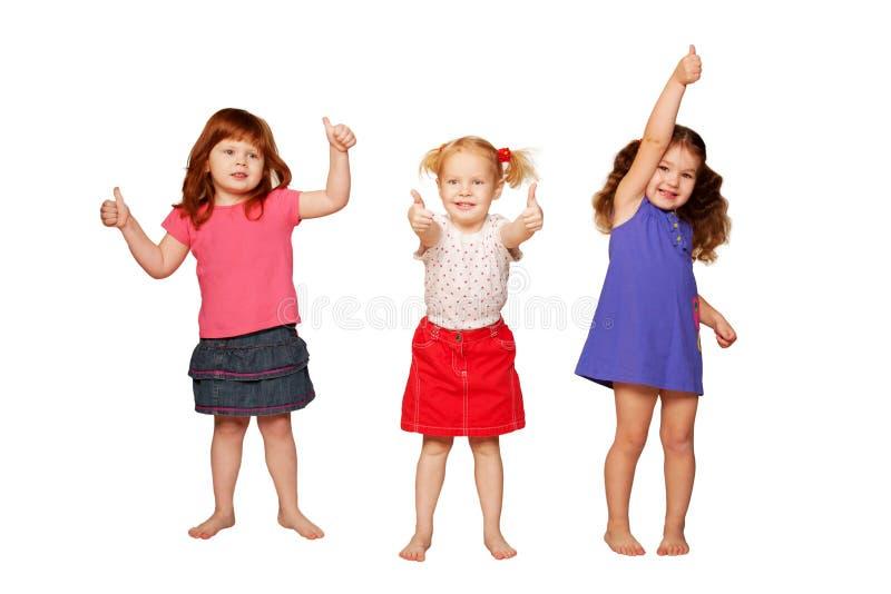 Маленькие девочки показывая большие пальцы руки, ОДОБРЕННЫЙ знак стоковая фотография rf