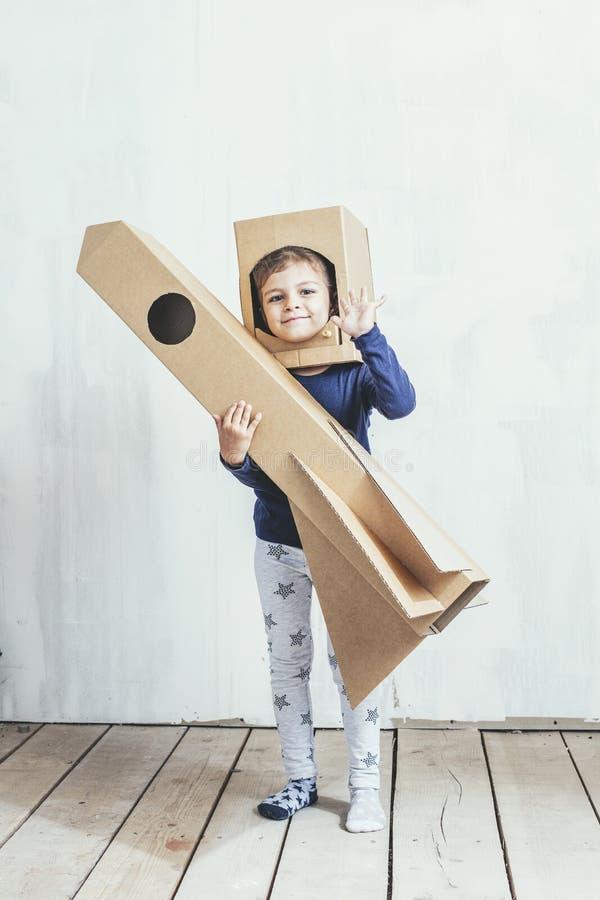 Маленькие девочки ребенка играя космонавта с ракетой картона и стоковое изображение rf