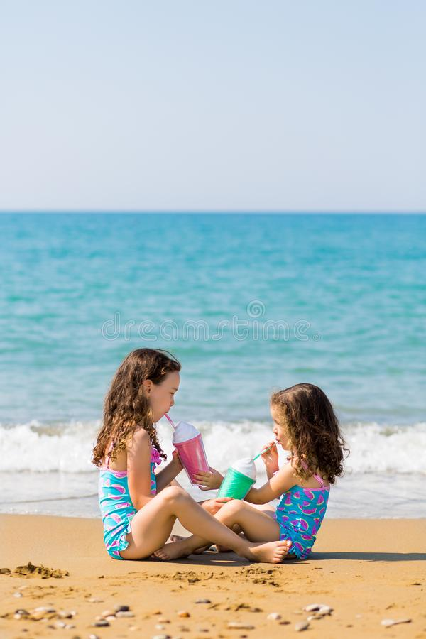 Маленькие девочки сидят для того чтобы сидеть противоположные один другого и напиток от покрашенной красивой концепции семейного  стоковая фотография rf