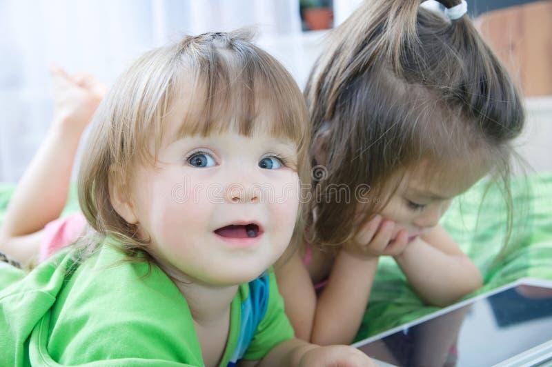 Маленькие девочки смотря на пусковой площадке лежа на кровати дома Трата времени детей стоковые изображения