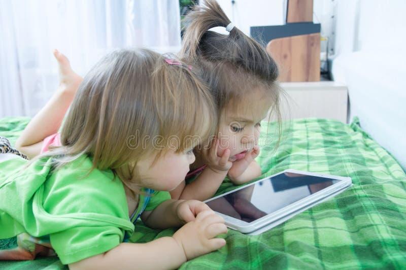 Маленькие девочки смотря на пусковой площадке лежа на кровати дома Трата времени детей стоковые фото