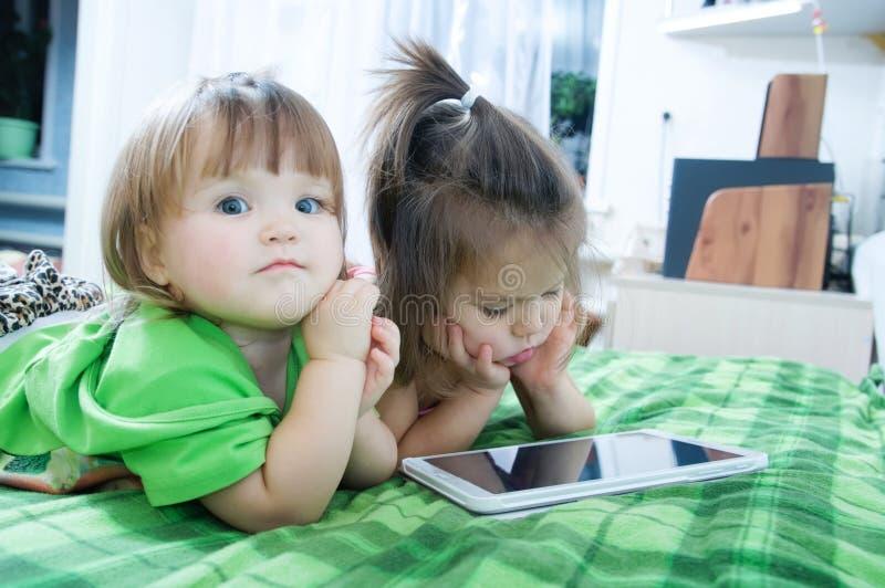 Маленькие девочки смотря на пусковой площадке лежа на кровати дома Трата времени детей стоковое изображение rf
