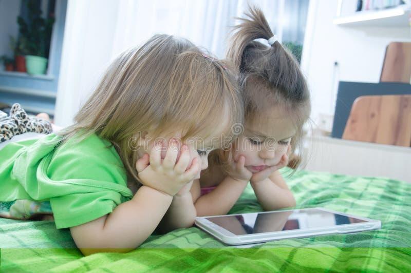 Маленькие девочки смотря на пусковой площадке лежа на кровати дома Трата времени детей Дети используя таблетку стоковые фотографии rf