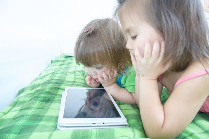 Маленькие девочки смотря на пусковой площадке лежа на кровати дома Трата времени детей Дети используя таблетку стоковые фото