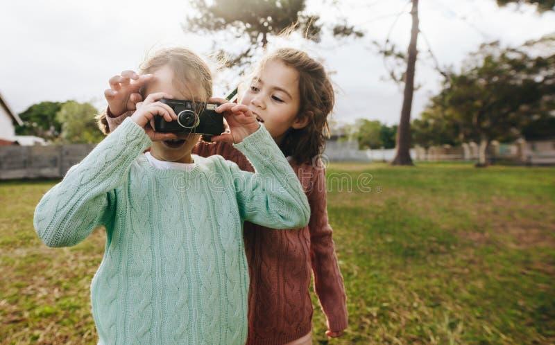 Маленькие девочки фотографируя с камерой на парке стоковые фотографии rf