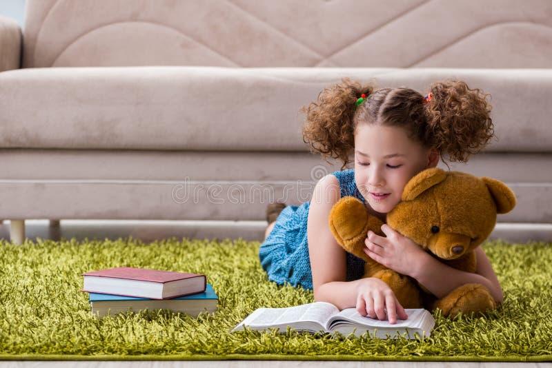 Маленькие милые книги чтения девушки дома стоковые изображения