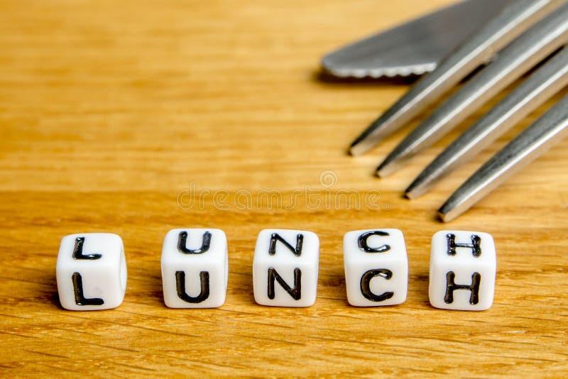 Маленькие миниатюрные figurines с немногим dices формировать обед слова как часть изображений собрания встречи команды стоковое изображение