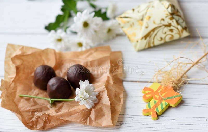 Маленькие присутствующие, свежие цветки и некоторые конфеты шоколада на белой деревянной поверхности стоковое изображение