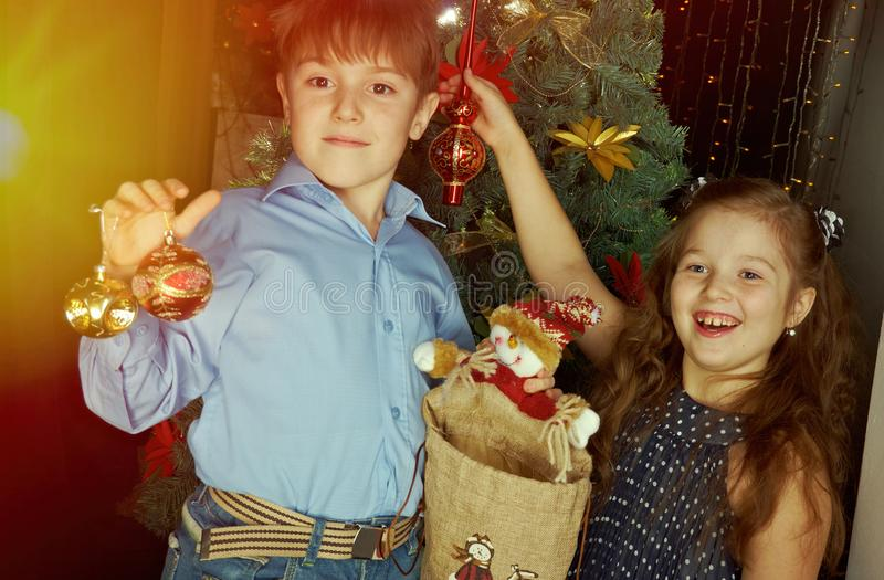 Маленькие ребеята украшают рождественскую елку стоковое фото