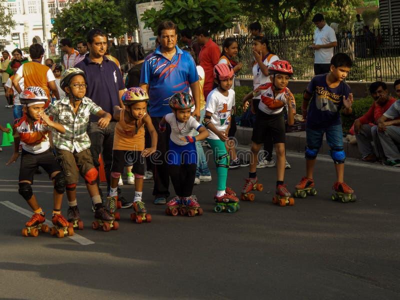 Маленькие ребята наслаждаясь кататься на коньках с их родителями стоковое фото