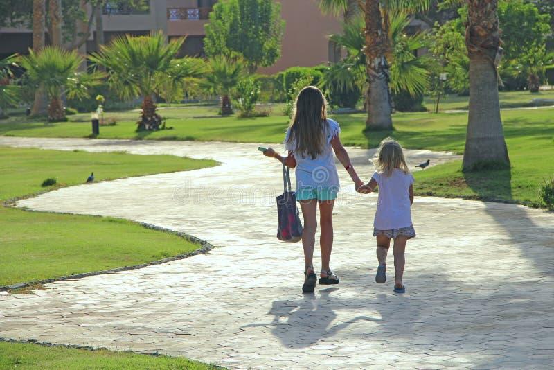 Маленькие туристы идут на дорогу в курортном городе держа рука об руку принципиальная схема ослабляя стоковые изображения