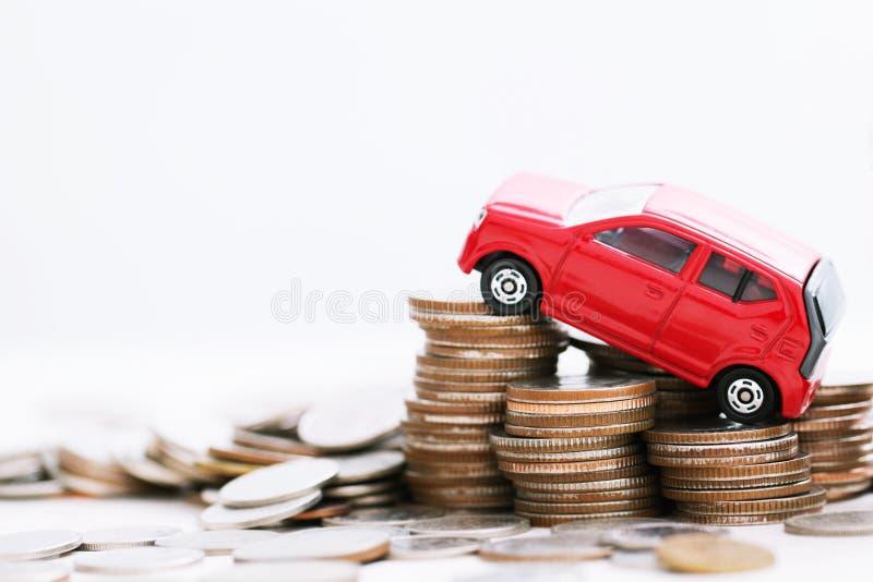 Маленький автомобиль игрушки над много монетками штабелированными деньгами для банковских ссуд стоит финансы стоковое фото rf