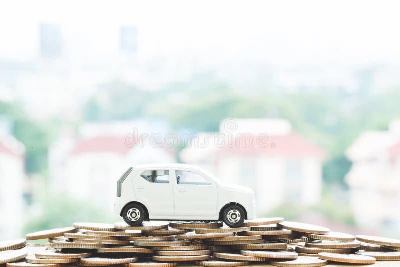Маленький автомобиль над много монетками штабелированными деньгами для банковских ссуд стоит финансы стоковое изображение