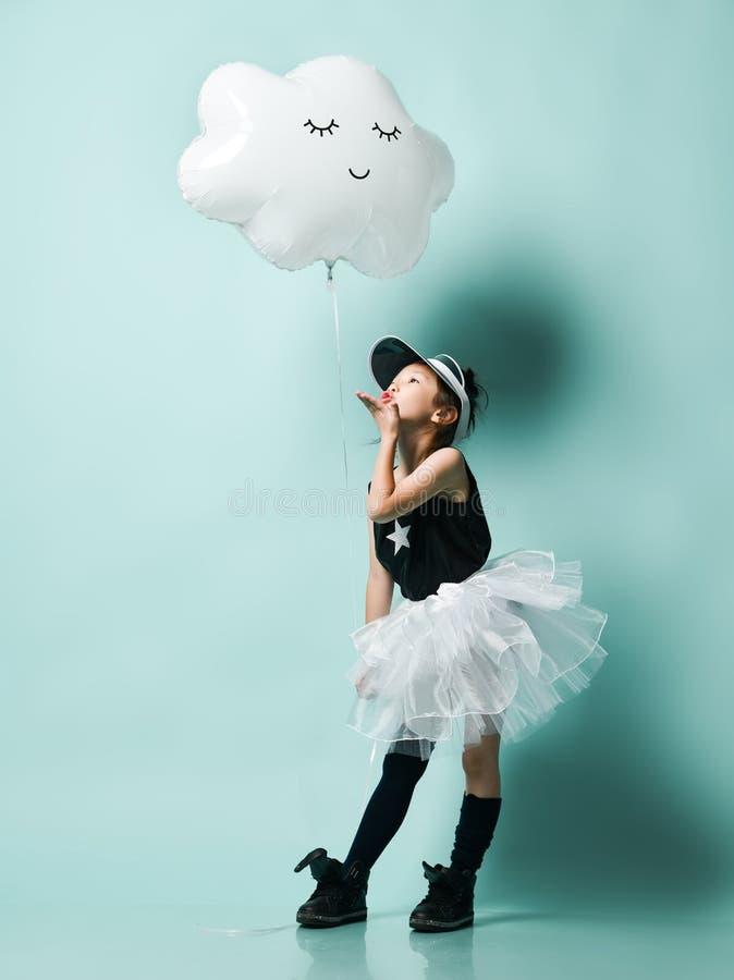 Маленький азиатский ребенк девушки в юбке моды держит металлический воздушный шар облака спать для дня рождения детей и отправляе стоковое изображение