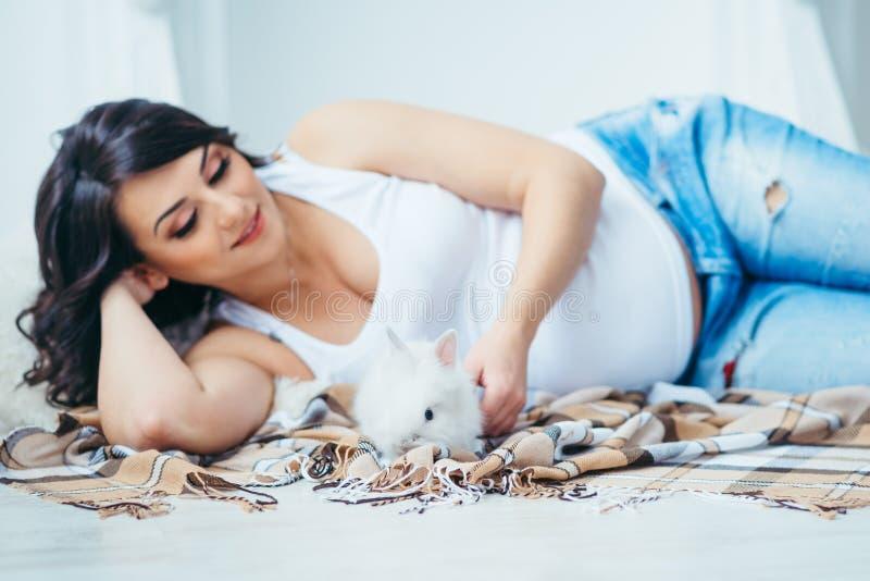Маленький белый пушистый кролик на запачканной предпосылке красивой усмехаясь беременной женщины играя с ним пока стоковые изображения rf