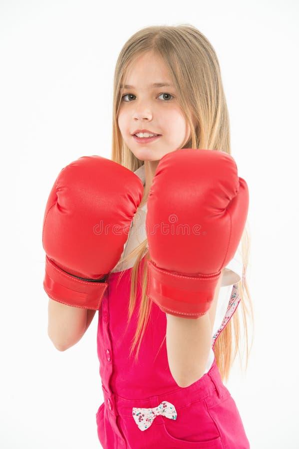Маленький боец перед боем Девушка при длинные светлые волосы нося огромные красные перчатки бокса, концепцию спорта Ребенк в пинк стоковое изображение