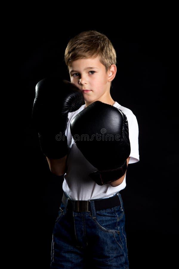 Маленький боксер стоя в черных перчатках бокса и он подготавливают для боя стоковые изображения