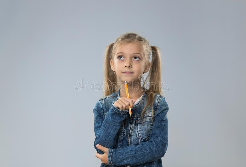 Маленький девочка-подросток в пальто джинсов, малый ребенк смотря, что вверх скопировал космос думает владение Chin стоковое фото rf