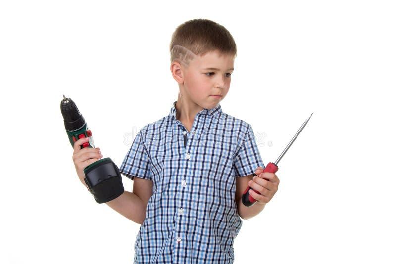 Маленький заботливый построитель мальчика в checkered рубашке держит сверло и отвертку в его руках, изолированных на белизне стоковая фотография rf