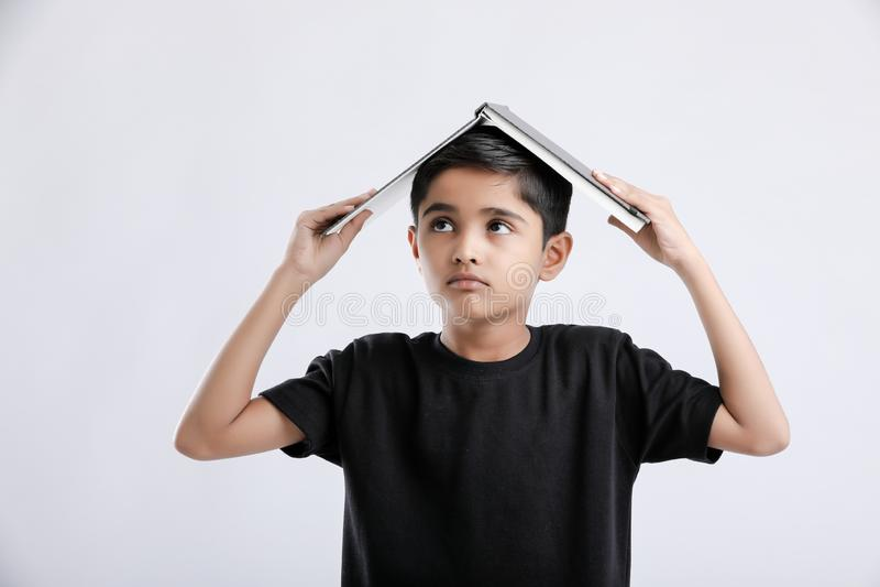 маленький индийский/азиатский мальчик с книгой на голове и мысли серьезной стоковая фотография