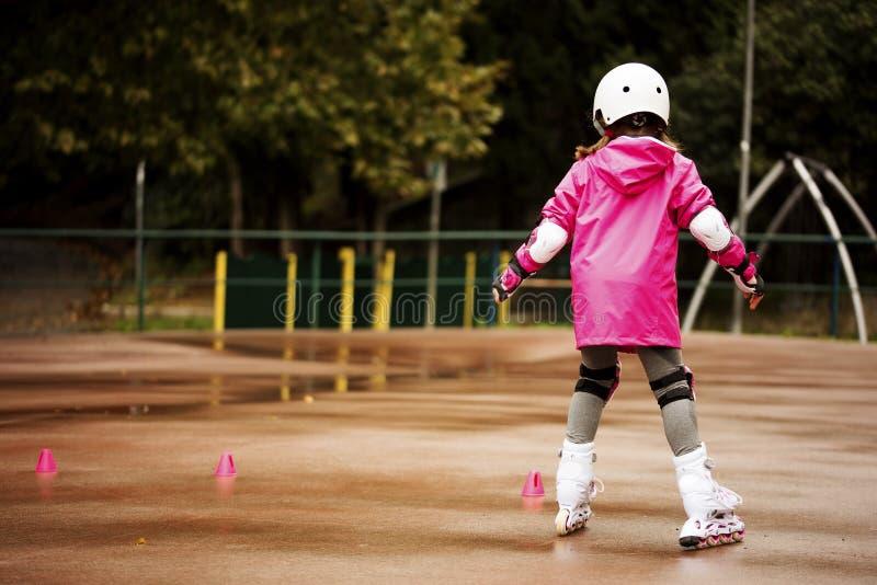 Маленький кавказский ролик beginner девушки в парке осени в дождливом дне стоковые фото