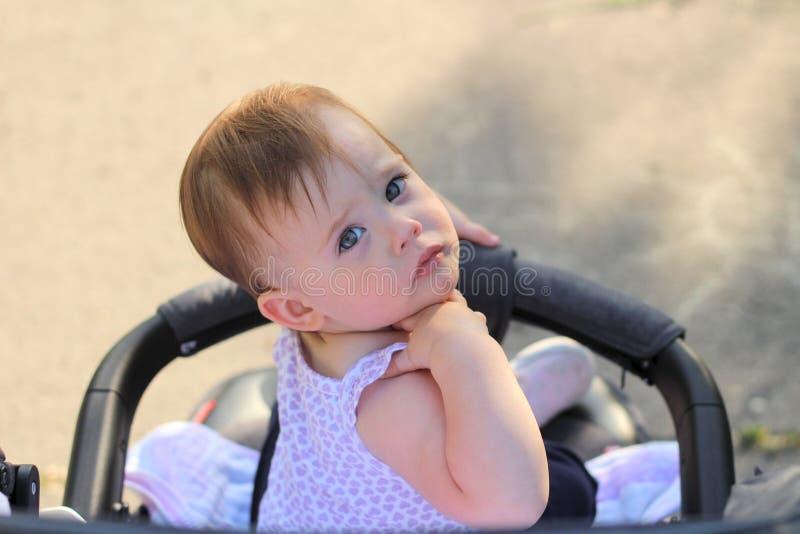 маленький, красивый, усмехающся, милый младенец redhead в безрукавной рубашке во вне--дверях pram падает руки вниз и смотрящ наза стоковые изображения rf