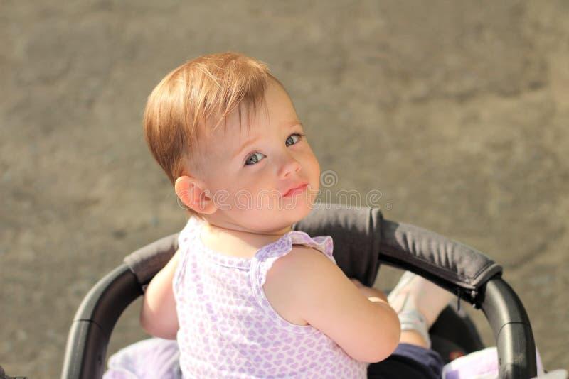 маленький, красивый, усмехающся, милый младенец redhead в безрукавной рубашке во вне--дверях pram падает руки вниз и смотрящ наза стоковые фото