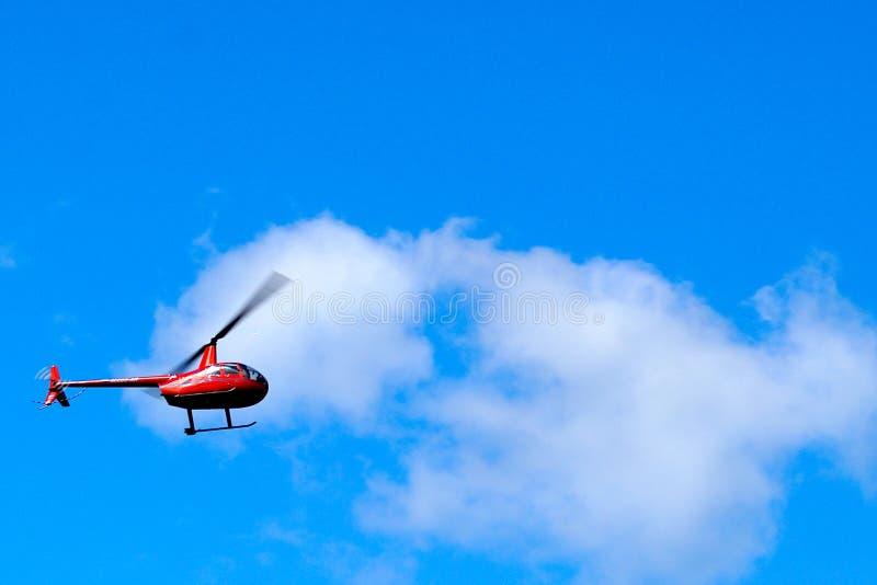 Маленький красный вертолет летит по голубому небу с белыми облаками стоковые фото