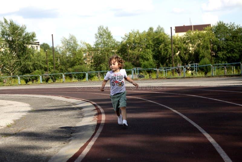 Маленький курчавый мальчик на третбане на стадионе, для здорового образа жизни стоковое фото rf