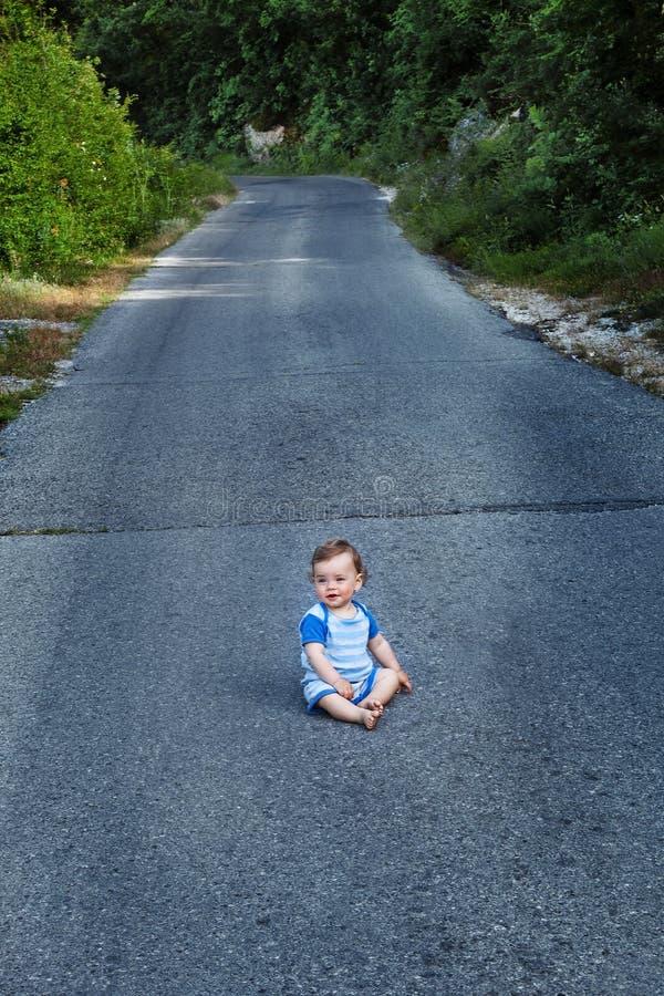Маленький курчавый мальчик сидя на середине дороги на летний день Вертикальная рамка стоковые изображения