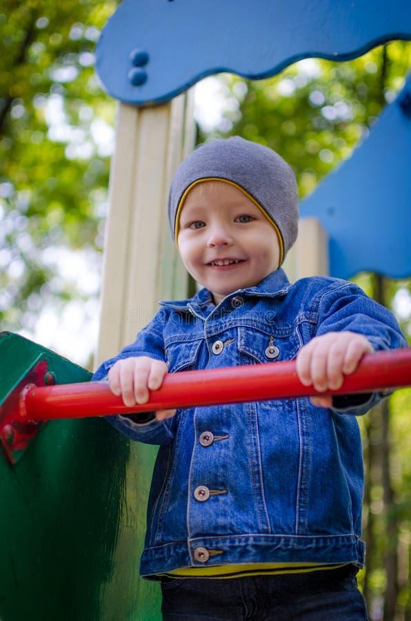 Маленький мальчик малыша имея потеху на спортивной площадке стоковое фото