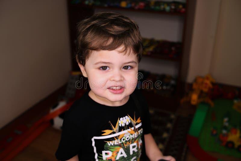 Маленький милый мальчик в черный усмехаться футболки стоковые изображения rf