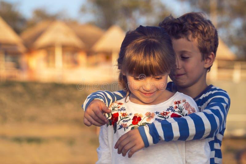 Маленький милый мальчик обнимая красивую девушку стоковые фотографии rf