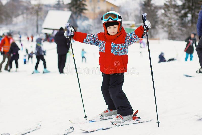 Маленький милый мальчик с лыжами и обмундированием лыжи Маленький лыжник в стоковое изображение