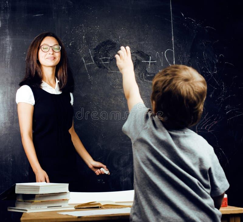 Маленький милый мальчик с молодым учителем в изучать класса, lifest стоковая фотография rf