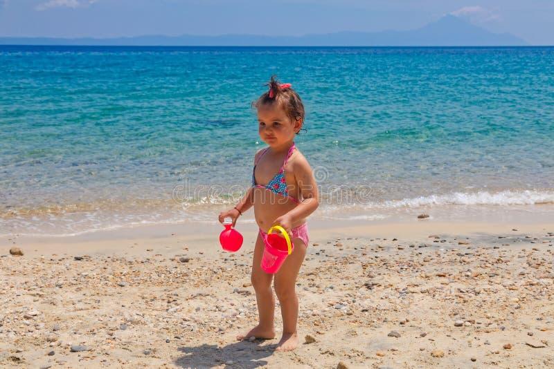 Маленький милый ребенок играет на пляже около моря на празднике стоковое фото