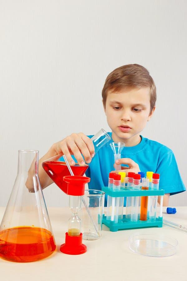 Маленький милый химик делая химические эксперименты в лаборатории стоковая фотография