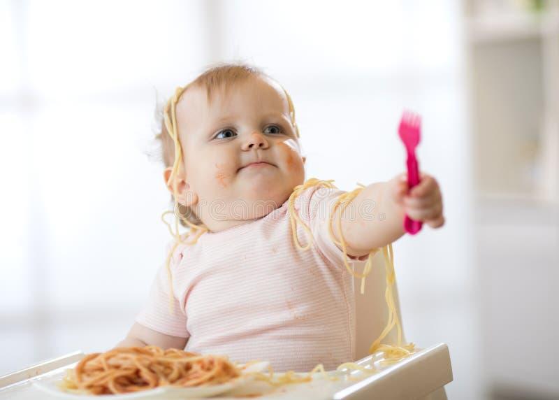 Маленький младенец есть ее макаронные изделия и делая беспорядок стоковая фотография rf