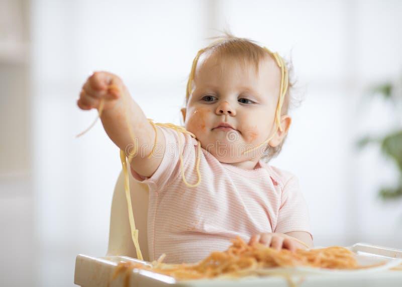 Маленький младенец есть ее обед и делая беспорядок стоковые фото